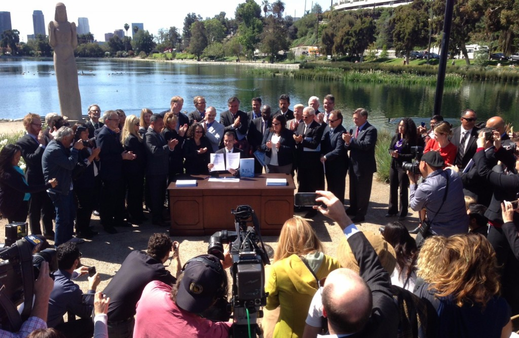 LA Mayor signing at outdoor desk in front of lake